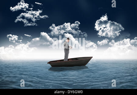 Composite image of standing businessman typing on his laptop in a sailboat - Stock Photo