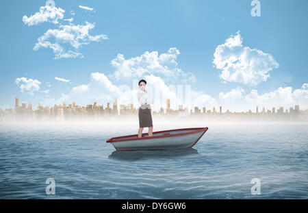 Composite image of elegant businesswoman standing with arms crossed in a sailboat - Stock Photo
