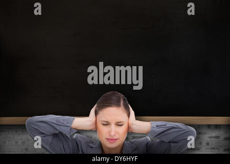 Composite image of close up of annoyed tradeswoman covering her ears - Stock Photo