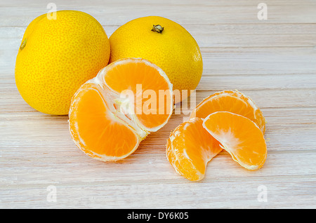group of tangerines, one peeled and separated into segments on the white kitchen table - Stock Photo