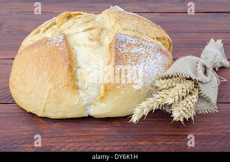 Traditional round bread with a few ears of wheat on a wooden table - Stock Photo