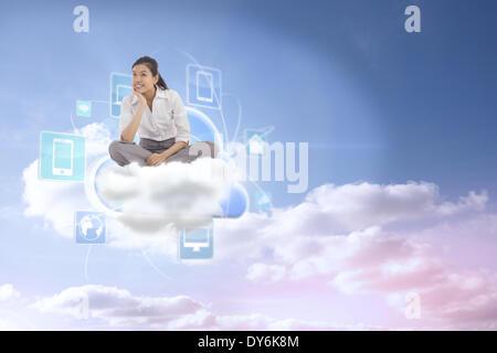 Composite image of businesswoman sitting cross legged thinking - Stock Photo