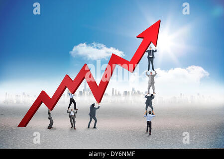 Composite image of business team holding up arrow - Stock Photo