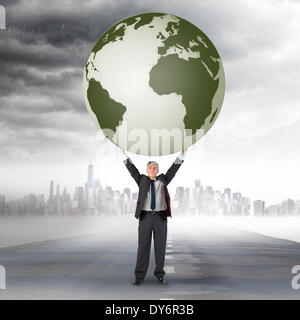 Composite image of businessman holding earth - Stock Photo
