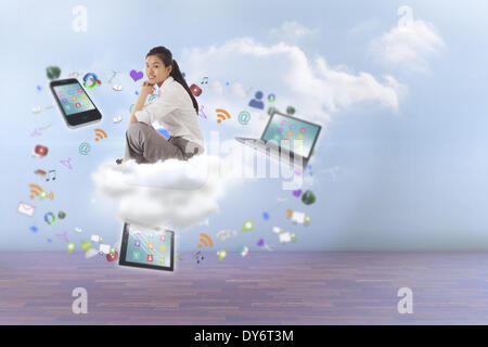 Composite image of businesswoman sitting cross legged with hands together - Stock Photo