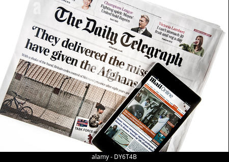 Touchscreen digital tablet with online news of Mail Online on top of British The Daily Telegraph newspaper on white - Stock Photo