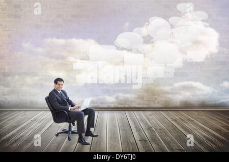 Composite image of young businessman sitting working with a laptop - Stock Photo