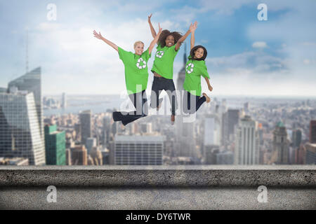 Composite image of enviromental activists jumping and smiling - Stock Photo