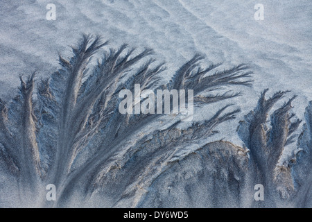 Abstract patterns in the sea sand from water erosion at beach along the coast in winter - Stock Photo