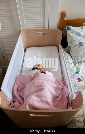 Three day old newborn baby girl asleep in her crib - Stock Photo