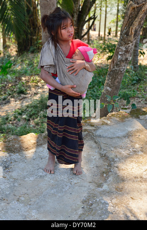 Hmong tribe child carrying a baby in a sling in a village on the Mekong Riverbank in Laos, Lao - Stock Photo