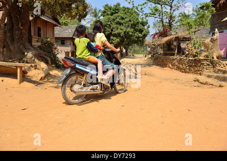 Three Hmong tribe village children set off on a motorbike -on route along the Mekong River banks .Laos - Stock Photo