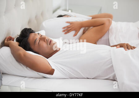 Woman covering her ears as partner is snoring loudly - Stock Photo