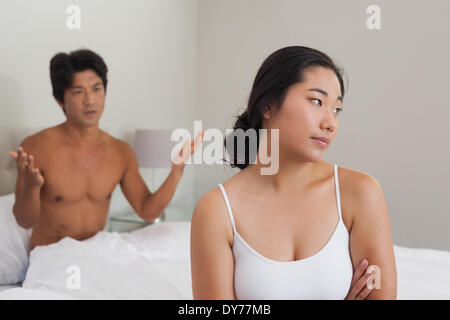 Couple having an argument in bed - Stock Photo