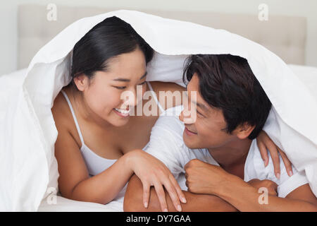 Happy couple lying on bed together under the duvet - Stock Photo