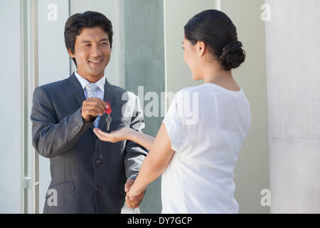 Smiling estate agent giving the key to buyer - Stock Photo
