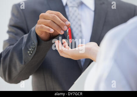Estate agent giving the key to buyer - Stock Photo