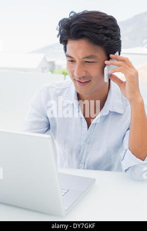 Smiling man using his laptop and talking on phone - Stock Photo