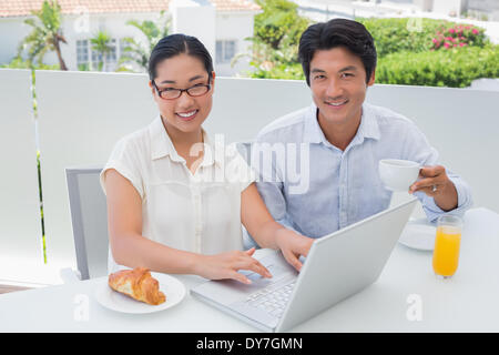 Smiling couple having breakfast together using laptop - Stock Photo