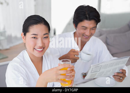 Couple in bathrobes spending the morning together - Stock Photo