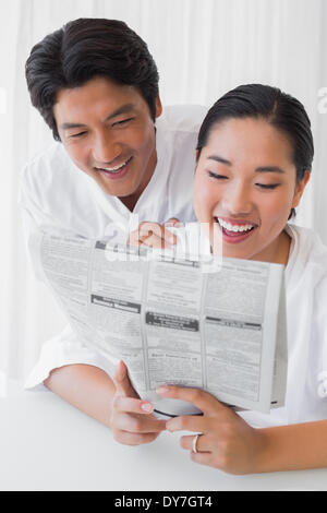 Couple in bathrobes reading newspaper together in the morning - Stock Photo