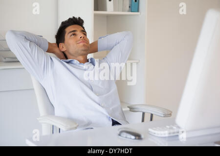 Casual businessman relaxing at desk leaning back - Stock Photo