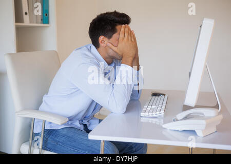 Casual businessman sitting at desk with head in hands - Stock Photo
