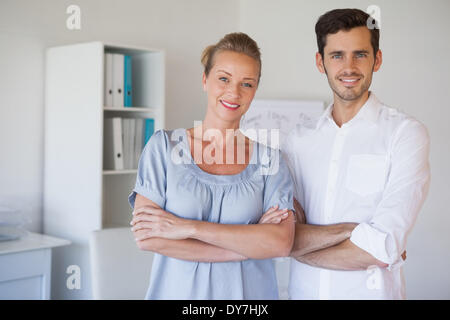 Casual business team smiling at camera with arms crossed - Stock Photo