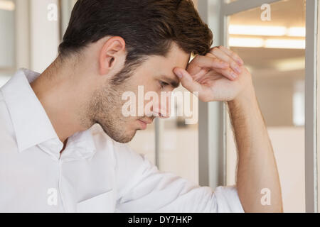 Casual businessman leaning on window looking worried - Stock Photo