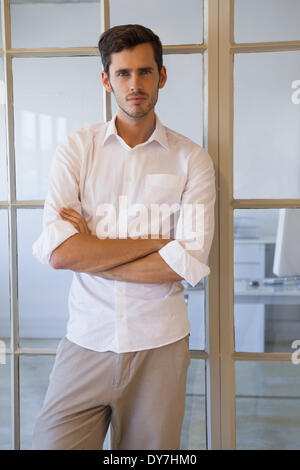 Casual businessman standing with arms crossed - Stock Photo