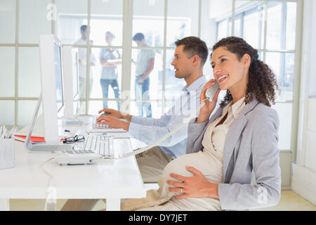 Casual pregnant businesswoman talking on phone at desk - Stock Photo