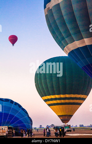 Hot air balloons being inflated and taking off for a sunrise flight from the West Bank of the Nile in Egypt. - Stock Photo