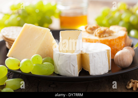 various types of cheese with grapes, honey and nuts - Stock Photo