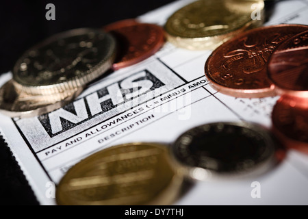 NHS Budget Cuts concept - A generic NHS payslip pay slip with British coins of the realm shot on a black background - Stock Photo