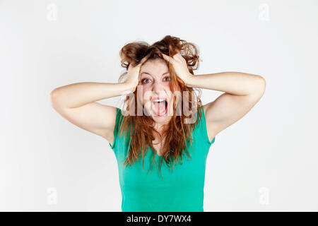 Desperate young woman tearing her hair - Stock Photo