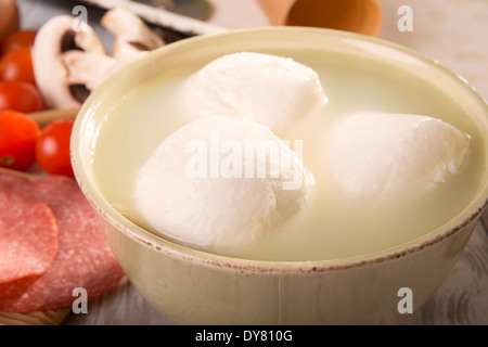 Bowl of three mozzarella balls in brine - Stock Photo