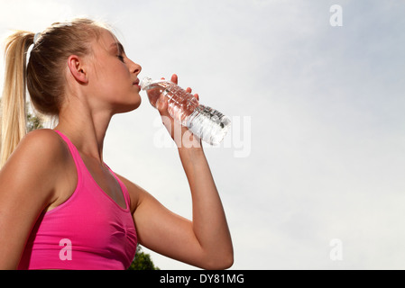 Young fitness woman drinking water after running - Stock Photo