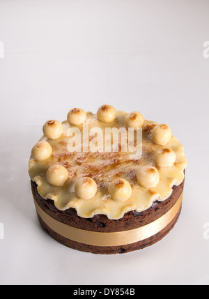 Simnel cake on a light background with fluted marzipan a yellow ribbon  with 11 marzipan balls 'portrait'   'cut - Stock Photo