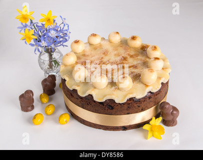 Simnel cake on a light background with fluted marzipan a yellow ribbon with 11 marzipan balls chocolate chicks flowers(26 - Stock Photo