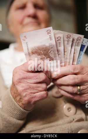 Senior woman holding euro notes - Stock Photo