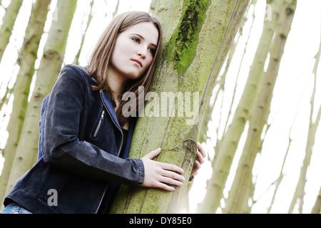 Portrait of teenage girl between tree trunks - Stock Photo