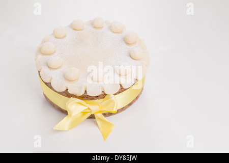 Simnel cake with basic marzipan decoration with a yellow ribbon round it sprinkled with icing sugar/powdered sugar(16 - Stock Photo