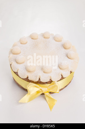 Simnel cake with basic marzipan decoration with a yellow ribbon sprinkled with icing sugar/powdered sugar,portrait - Stock Photo