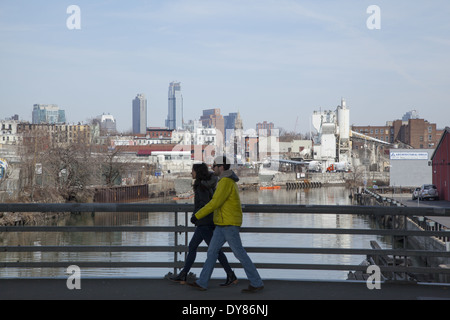 Two people walk on the 9th street bridge over the polluted Gowanus Canal in Brooklyn, New York. Environmental super - Stock Photo