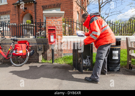 Royal Mail postman collecting post ready for delivery on his bike in the village of Plumtree, Nottinghamshire, England, - Stock Photo