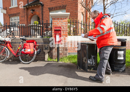 UK postman on his round in a rural area, collecting and delivering mail from a box outside the Old Post Office, - Stock Photo