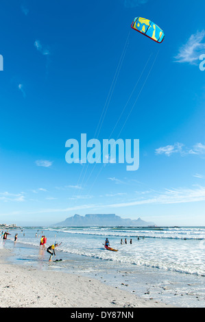 Kitesurfer preparing to surf, Bloubergstrand, Table Mountain in the background, South Africa - Stock Photo