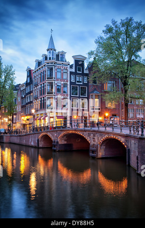 Amsterdam in the evening, old houses and bridge over canal, corner of Grimburgwal and Oudezijds Voorburgwal in Holland. - Stock Photo