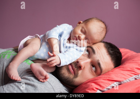 Newborn baby sleeping with father - Stock Photo