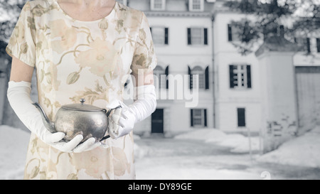 A woman in a floral dress holding a silver pot of tea in front of a white mansion. - Stock Photo